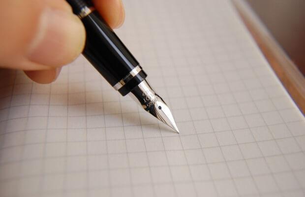 Pisanie piórem na arkuszu papieru