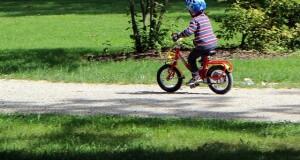 Chłopczyk na rowerku dziecięcym w parku