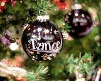 """Świąteczna bombka z napisem """"Dance"""" wisząca na choince"""