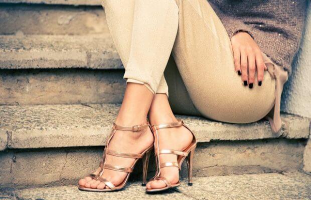 Kobieta w sandałkach na obcasie siedzi na schodach