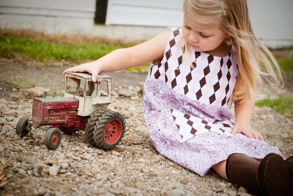 Dziewczynka bawi się ciągnikiem