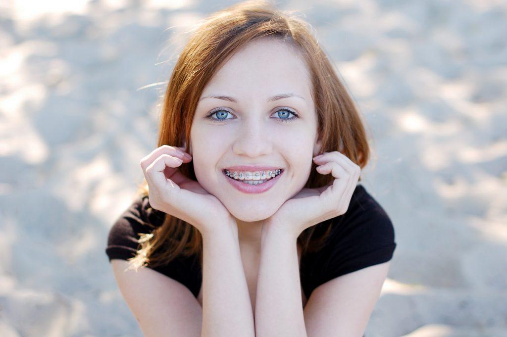 Uśmiechnięta dziewczyna z aparatem