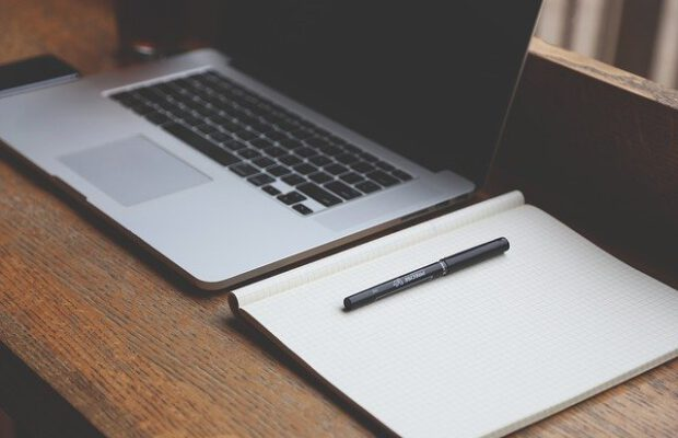 Zeszyt i komputer w domowym biurze