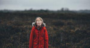 Chłopiec w czerwonej kurtce wystawiający język